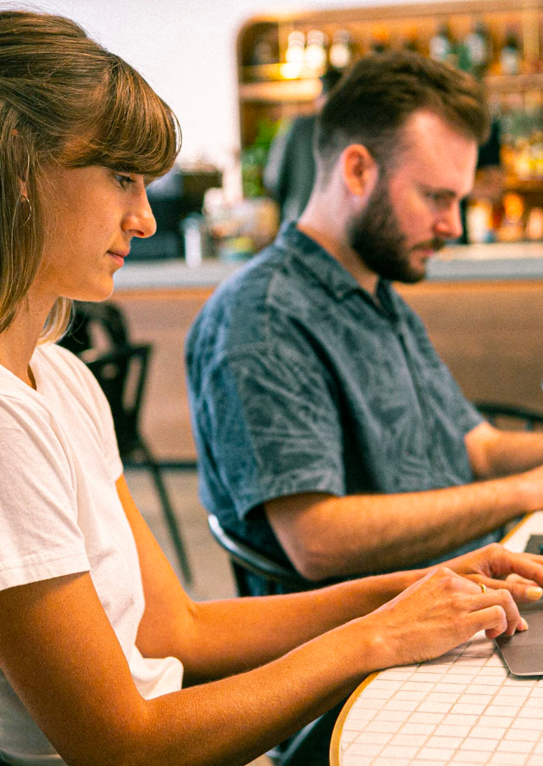 Two people sitting on a desk, typing on a laptop